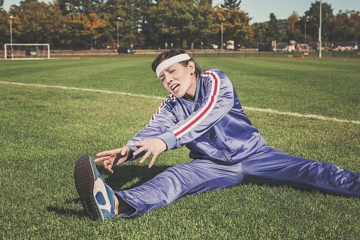 אישה במדי ספורט מתאמצת להתמתח על דשא