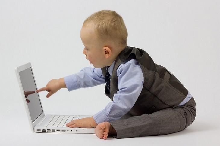 תינוק יושב על הרצפה ונוגע במסך של מחשב נייד