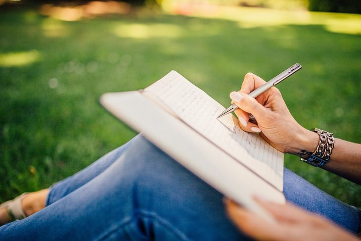 אישה יושבת על דשא וכותבת במחברת
