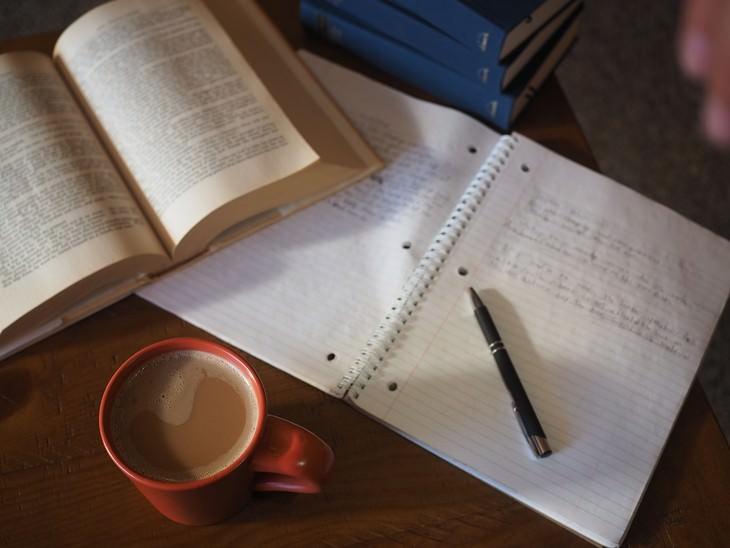 מחברת עם עט עליה לצד ספר פתוח וכוס קפה
