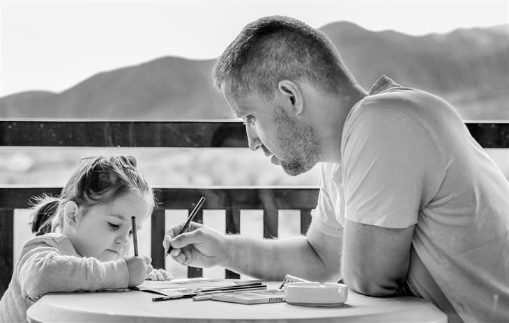 אבא ובת יושבים מול שולחן, כשהיא כותבת על דף והוא עוזר לה