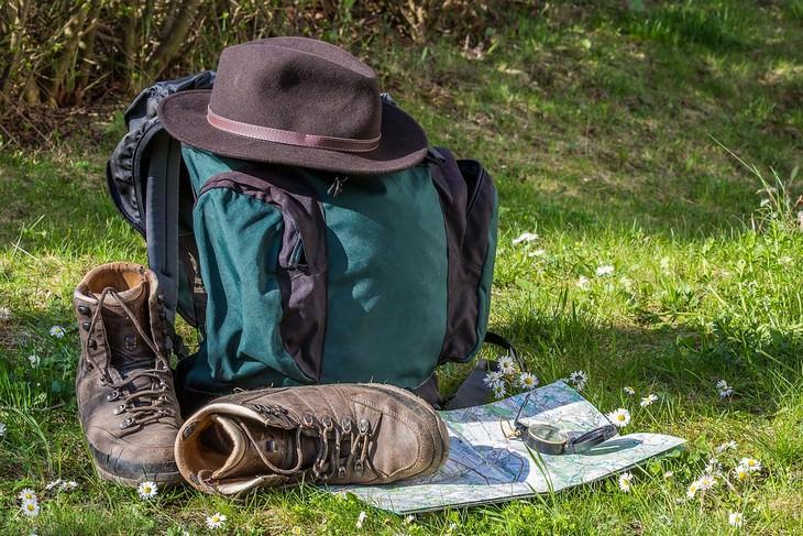 תיק טיולים מונח על דשא כשעליו נעלי הליכה ומולו מפה עם מצפן עליה