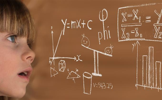 ילדה מסתכלת על לוח מלא בנוסחאות ושרטוטים
