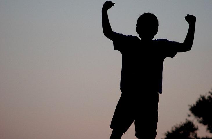 ילד מרים את ידיו באוויר