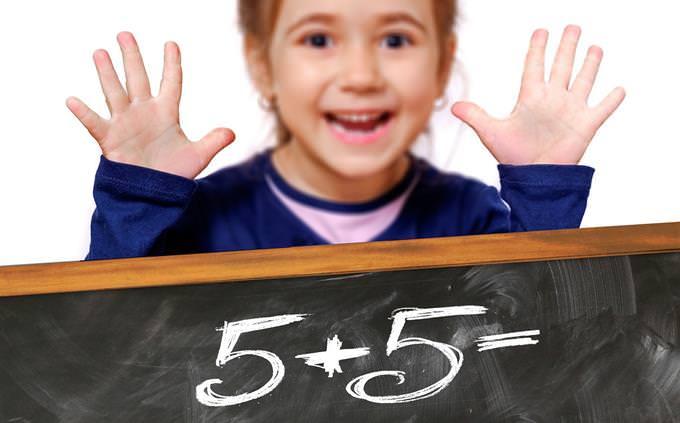 ילד עומדת מאחורי לוח שעליו רשום 5+5 והיא מראה 10 אצבעות