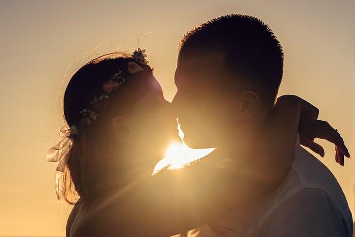 זוג חבוק מתנשק על רקע שקיעה