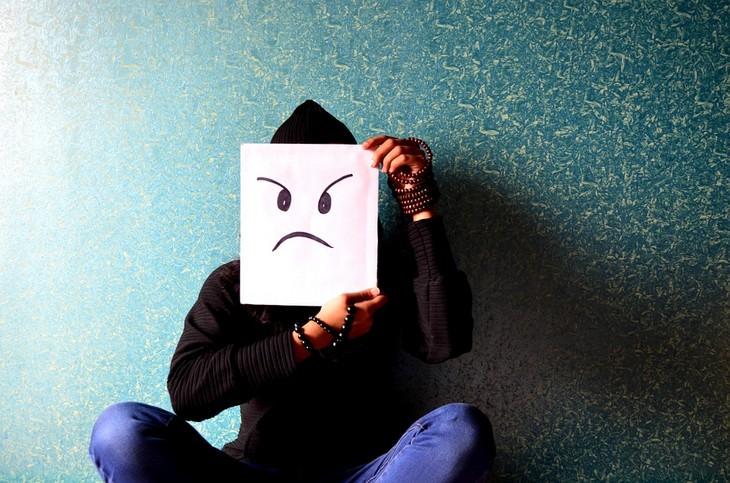 אדם מחזיק איור עם פרצוף כועס מול פניו
