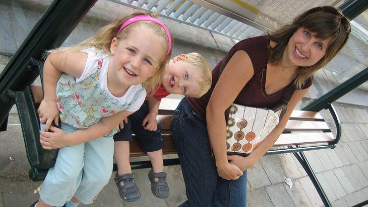 אם יושבת על ספסל עם שתי בנותיה