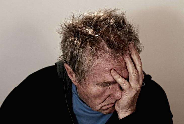אדם מבוגר אוחז בראשו בידו