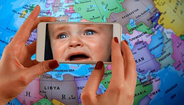 ילד בוכה מצולם בסמארטפון על רקע הגלובוס