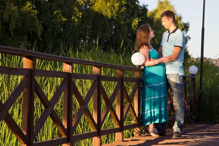 אישה בהריון ובן זוגה עומדים פנים מול פנים על גשר ואוחזים ידיים