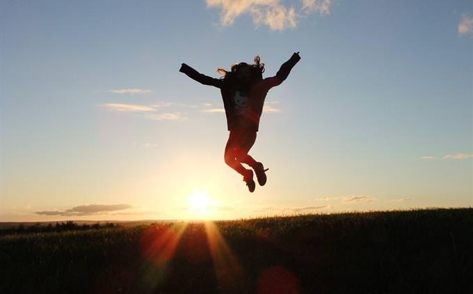 אישה קופצת על רקע שקיעה
