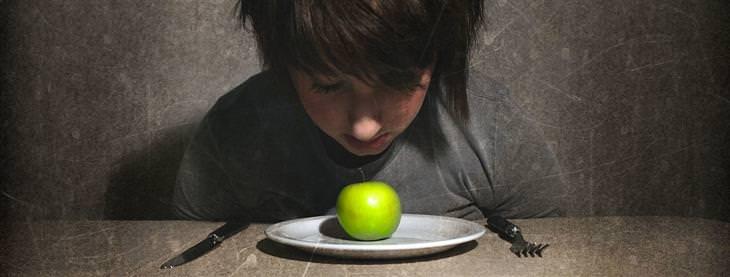 אישה יושבת מול צלחת שעליה תפוח קטן