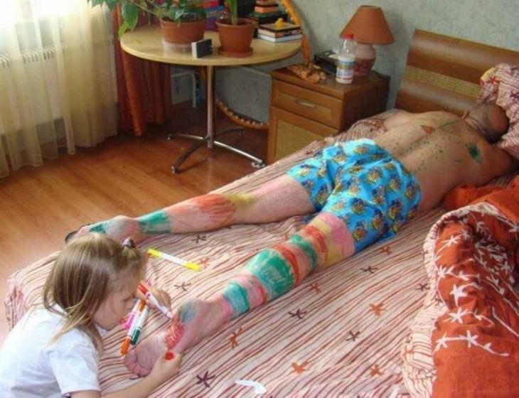 ילדה צובעת את הרגליים של אבא שלה שישן