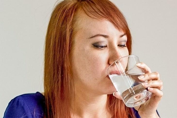 אישה שותה מים מכוס זכוכית