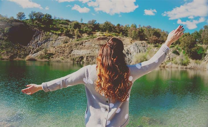 אישה עומדת מול אגם ומרימה את ידיה לצדדים