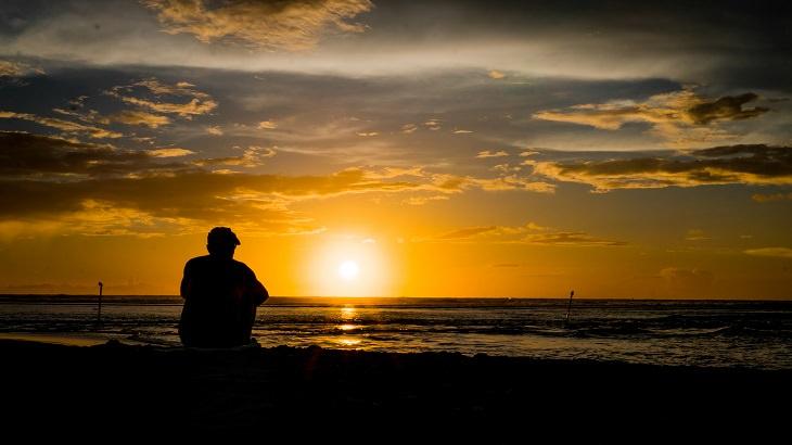 גבר מבוגר על חוף בזמן שקיעה