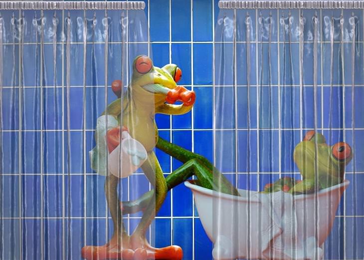 פסלים של צפרדעים מצחצחים שיניים ושוכבים באמבטיה