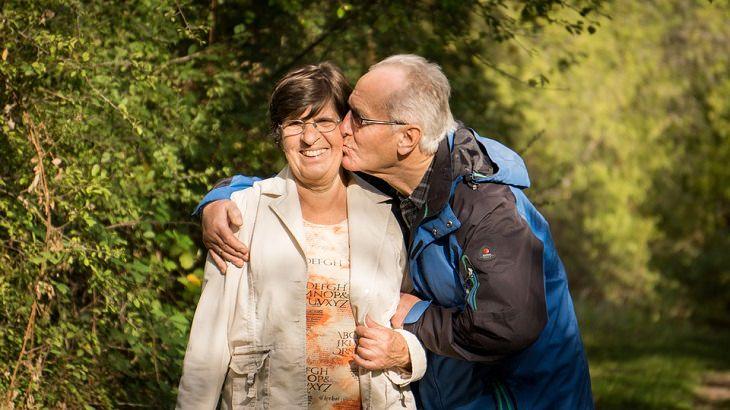 זוג מבוגר בחיק הטבע והגבר מנשק את האישה על הלחי