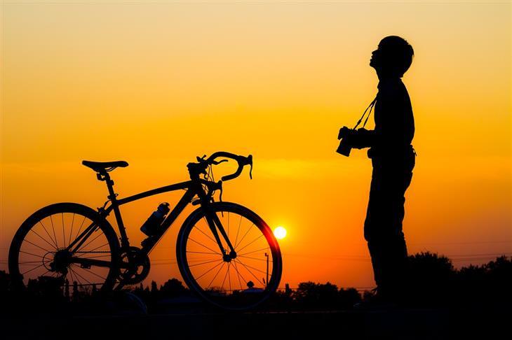 צללית של איש עם מצלמה עומד מול האופניים וברקע שקיעה