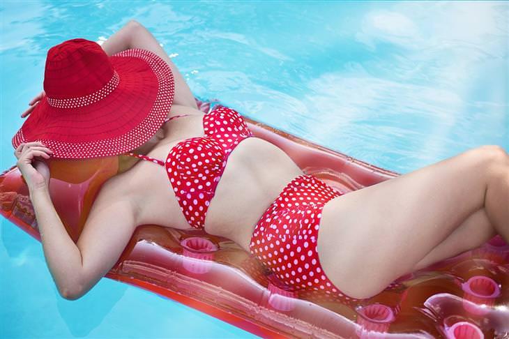 אישה שוכבת על מזרן צף במים