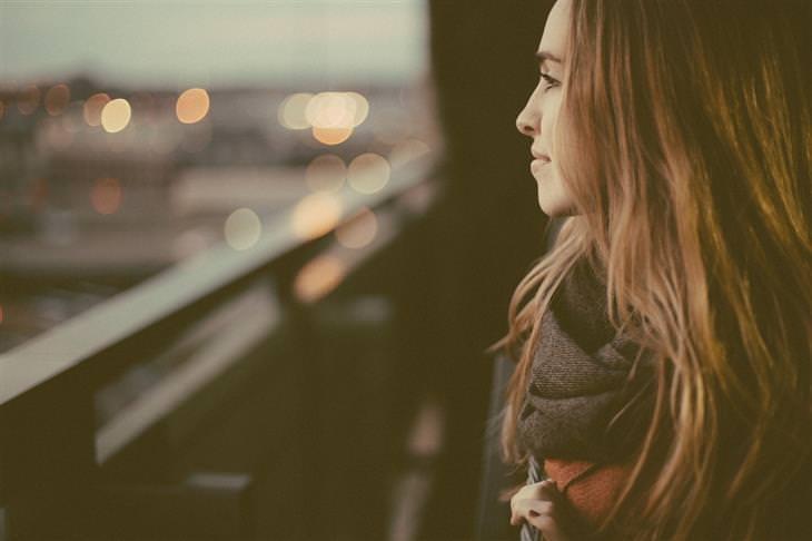 אישה מחייכת ומביטה מבעד לחלון