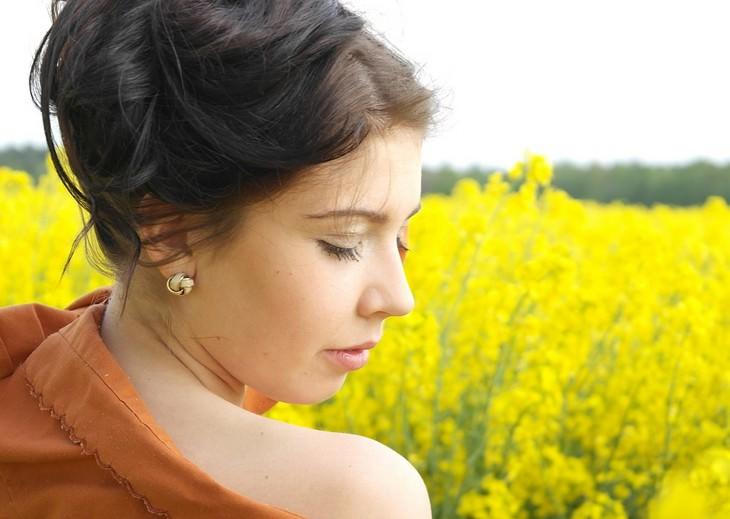 אישה עומדת באמצע שדה ועוצמת עיניים