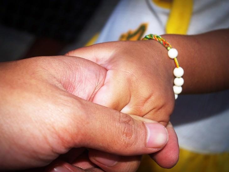 יד של גבר לוחצת יד של ילדה קטנה