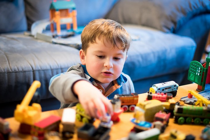 ילד קטן משחק בצעצועים שונים
