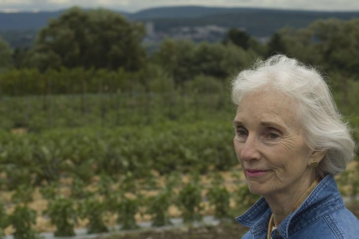 סודות הטיפוח של סבתא: אישה מבוגרת מחייכת בשדה