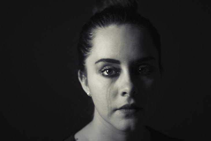 התמודדות עם כישלון: אישה דומעת וחצי מוארת מביטה למצלמה