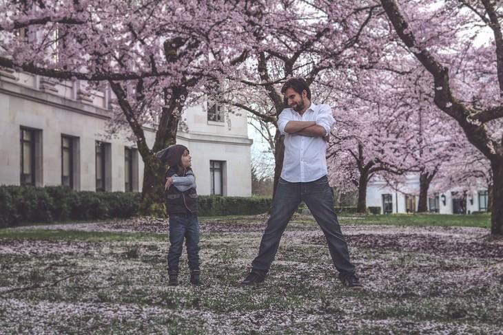 משא ומתן עם ילדים: אב ובן עומדים זה לצד זה עם ידיים שלובות