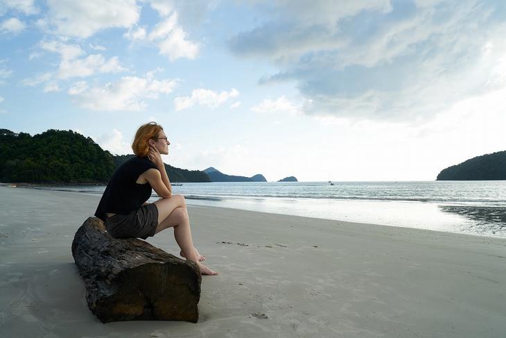 התמודדות עם כישלון: אישה יושבת על בול עץ בחוף ים ומביטה לאופק