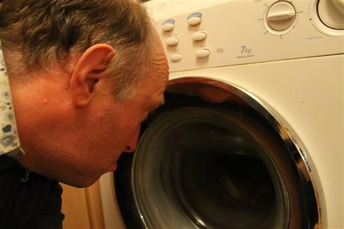 איש מסתכל בעצב על מכונת כביסה