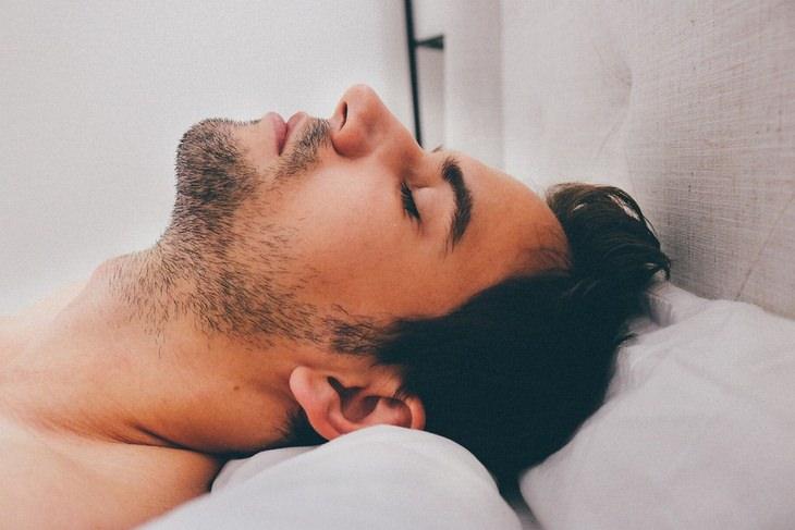 יתרונות השינה בעירום: ראש של גבר ישן במיטה