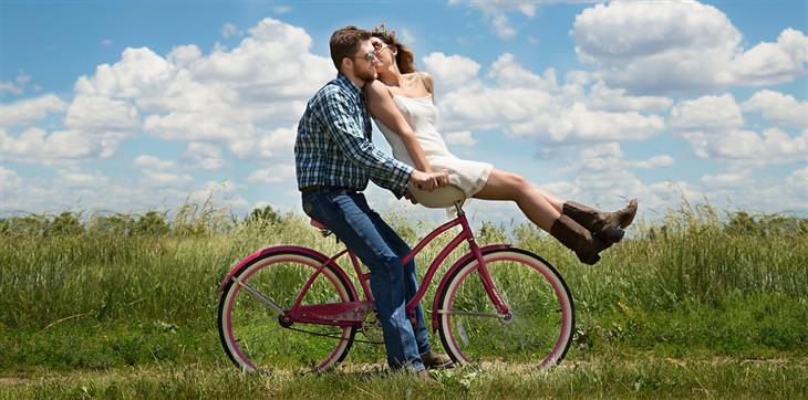 הזכויות שנולדנו איתן: גבר ואישה רוכבים על אופניים ביחד בשדה, והאישה מנשקת את הגבר