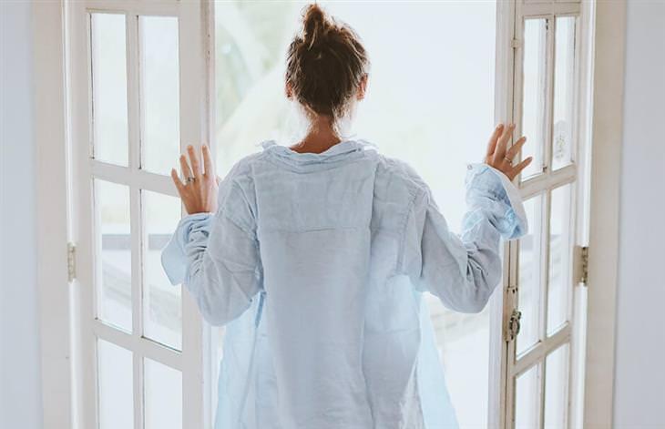 יתרונות השינה בעירום: אישה לבושה בחולצת גבר פותחת חלון בחדר השינה