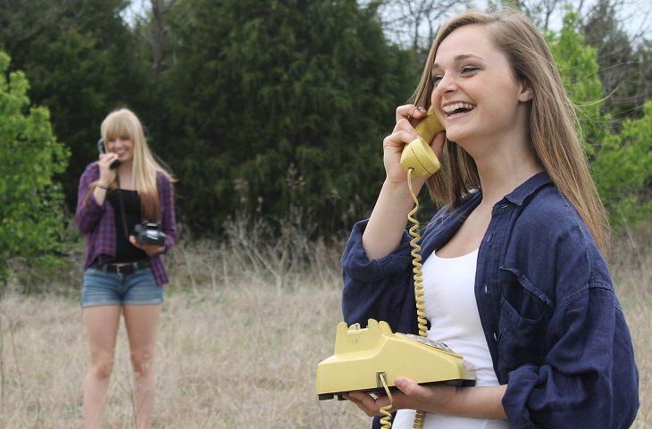 איך להחזיר את האושר: שתי בחורות מחייכות ואוחזות בטלפונים בשדה
