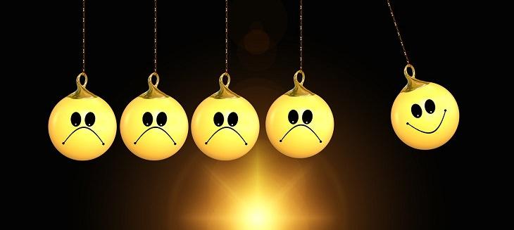 איך להחזיר את האושר: איור של מטוטלת המורכבת מפרצוף מחייך אחד ומספר פרצופים עצובים