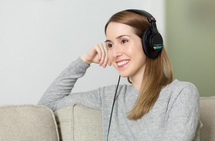 איך להחזיר את האושר: אישה מחייכת ומאזינה למוזיקה באוזניות