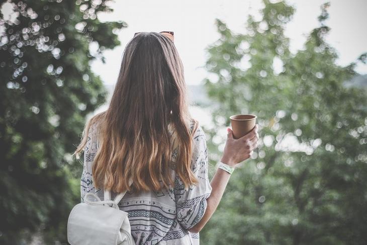אישה עם שיער שופע מחזיקה ספל בגבה למצלמה