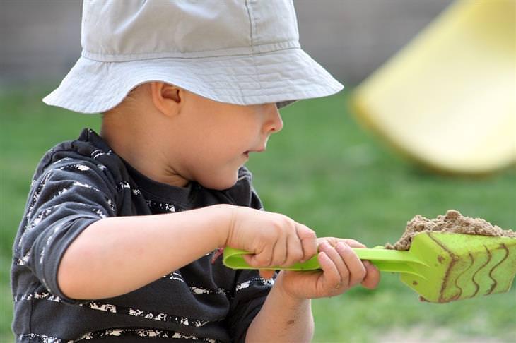 מצבים שמסכנים ילדים במגע עם חיידקים: ילד משחק עם חול בעזרת צעצוע את חפירה