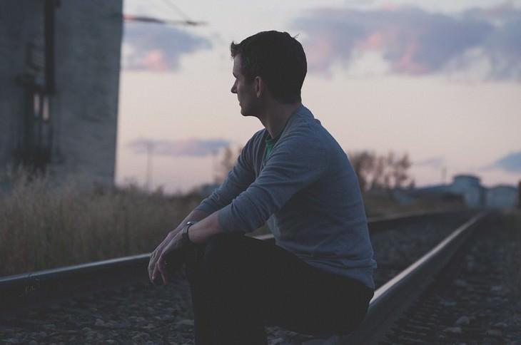 תרגילים לשיפור היציבה: גבר יושב על מסילת רכבת בגב כפוף ומביט קדימה