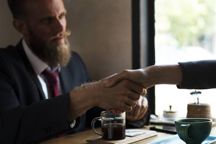 איש בחליפה לוחץ ידיים עם האדם שמולו הוא יושב