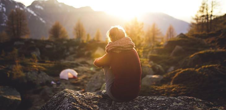 דברים שצריך לעשות כדי להמשיך הלאה: אישה יושבת בטבע ומסתכלת לכיוון השקיעה