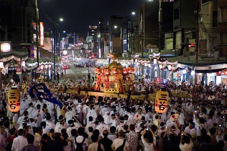פסטיבל גיון בקיוטו: רחוב הומה אדם ואנשים מניפים מעלה את אחת מקרונות המצעד