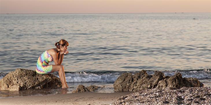 דברים שצריך לעשות כדי להמשיך הלאה: אישה יושבת על סלע בחוף הים ונראית מהורהרת
