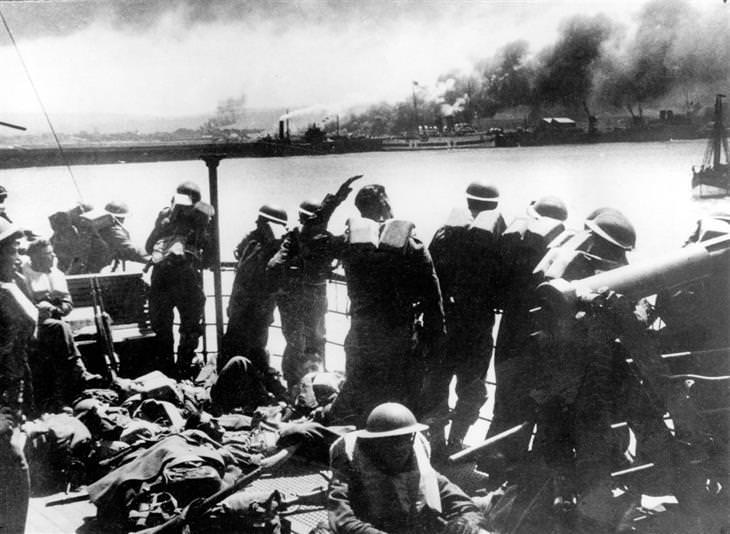 מבצע החילוץ בדנקרק: חיילים מביטים מספינה בלב ים על חופי דנקרק שעשן מיתמר מהם