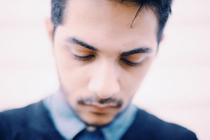 סימנים מבלבלים לאהבה בזוגיות: גבר משפיל את ראשו מטה