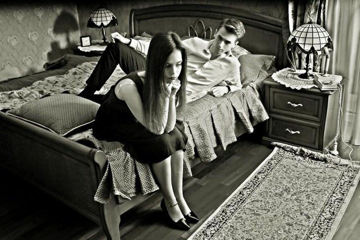 סימנים מבלבלים לאהבה בזוגיות: אישה עצובה יושבת על מיטה לצד בן זוגה